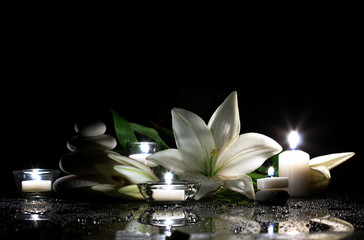 white lily, stones and candles