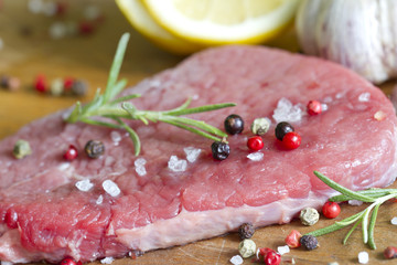Raw beef steak on cutting board with spices