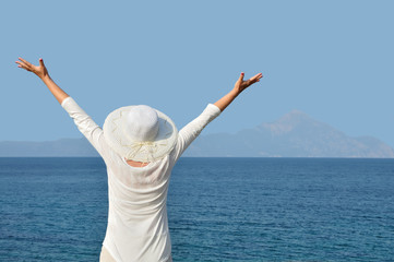 Woman wearing a hat with hands up facing the sea