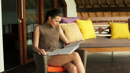 Beautiful woman reading magazine on terrace