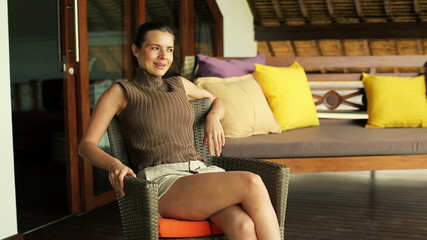 Beautiful woman sitting on chair and relaxing on terrace