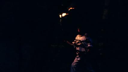 Peasant walking through dark forest using a wooden torch