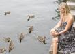 woman at a lake with ducks