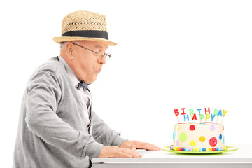 Senior blowing candles on his birthday cake