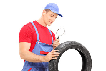 Mechanic examining tire through magnifying glass