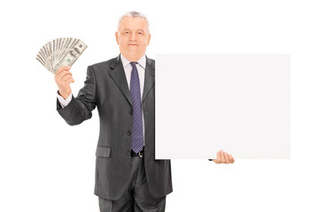Mature businessman holding money and blank banner