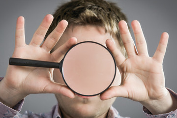 Man with magnifying glass showing teeth