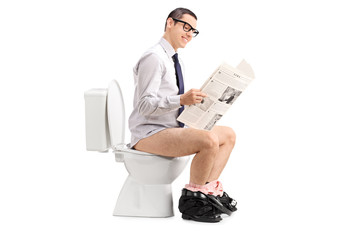 Man reading a newspaper seated on a toilet