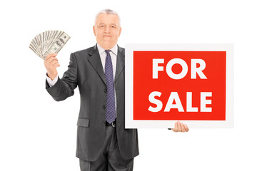 Mature businessman holding cash and for sale sign