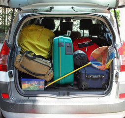 trunk of the car with fishing net and luggage bags ready for the