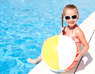 Smiling little girl with ball in swimming pool