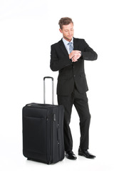 handsome guy standing with luggage in suit.