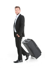 handsome guy walking with luggage and smiling.