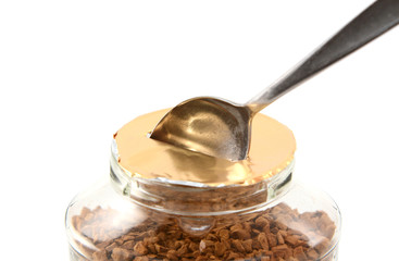 Teaspoon breaking the foil seal on a jar of coffee