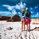 Couple at tropical beach wearing rash guard poster
