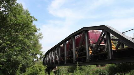Alter Personenzug fährt über eine Brücke