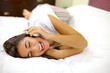 Happy woman smiling on the phone laying in bed