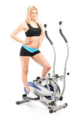 Active woman posing on a cross trainer machine