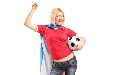 Cheerful female football fan holding a ball