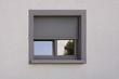 Dunkles Kunststofffenster mit Rollladen in grauer Fassade