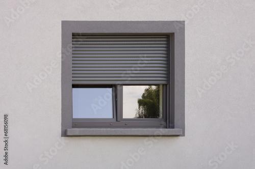 Dunkles Kunststofffenster mit Rollladen in grauer Fassade - 68156098