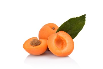 Three sliced apricots with leaf isolated on white