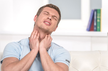 Portrait of handsome male with pain in throat.