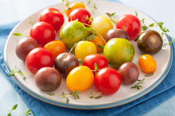 colorful tomatoes in plate on blue background