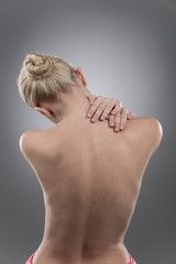 Woman massaging pain neck and back.