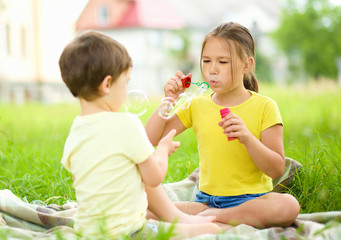 Little girl and boy are blowing soap bubbles