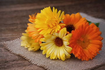 Bouquet of calendulas on canvas on old wooden background