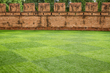 Grass field in front of ancient city wall