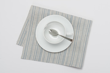 White Cup And Plate On Folded Natural Linen Napkin On White Back