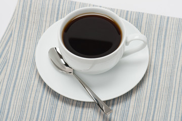 Black Coffee In White Cup On Folded Natural Linen Napkin. White