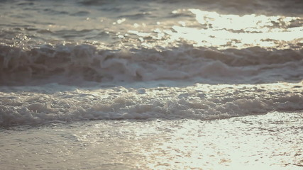 Beautiful young girl walking on the beach in the waves