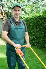 Gärtner mit Rasenmäher bei Garten-Pflege