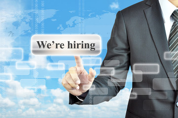 Businessman hand touching We're hiring  sign on virtual screen