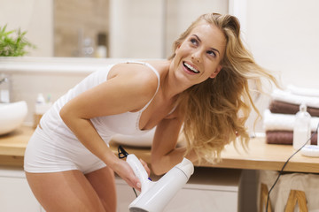 Blonde woman has fun during drying hair in bathroom .