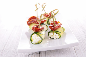 finger food, zucchini roll with cheese and dried tomatoes