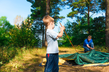 little son helps to establish a tent on the nature