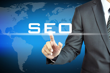 Businessman hand touching SEO (or Search Engine Optimization)