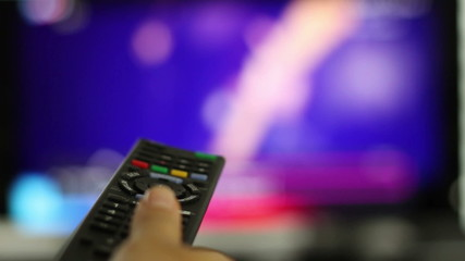 Watching TV and using remote controller, close up