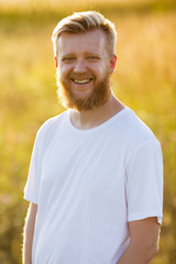 Happy young blond bearded man