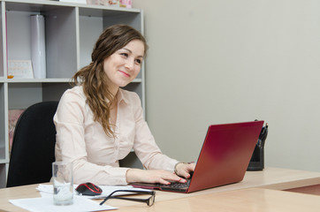 Young girl working at a laptop in the office
