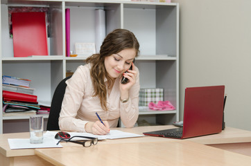 Business woman calling by phone and does records