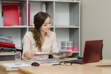 Business woman reading a magazine in the office