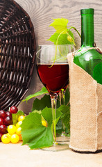 wine glass, bottle of wine and fruits on wooden background