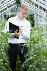 Taking notes in a greenhouse