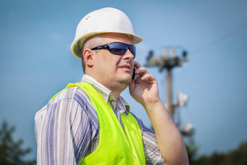 Worker with cell phone on a blue sky background