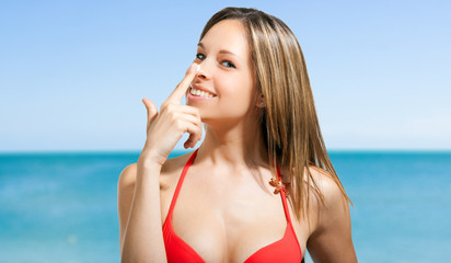 Woman applying the sunscreen